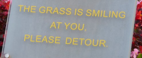 Sign saying 'The grass is smiling at you'